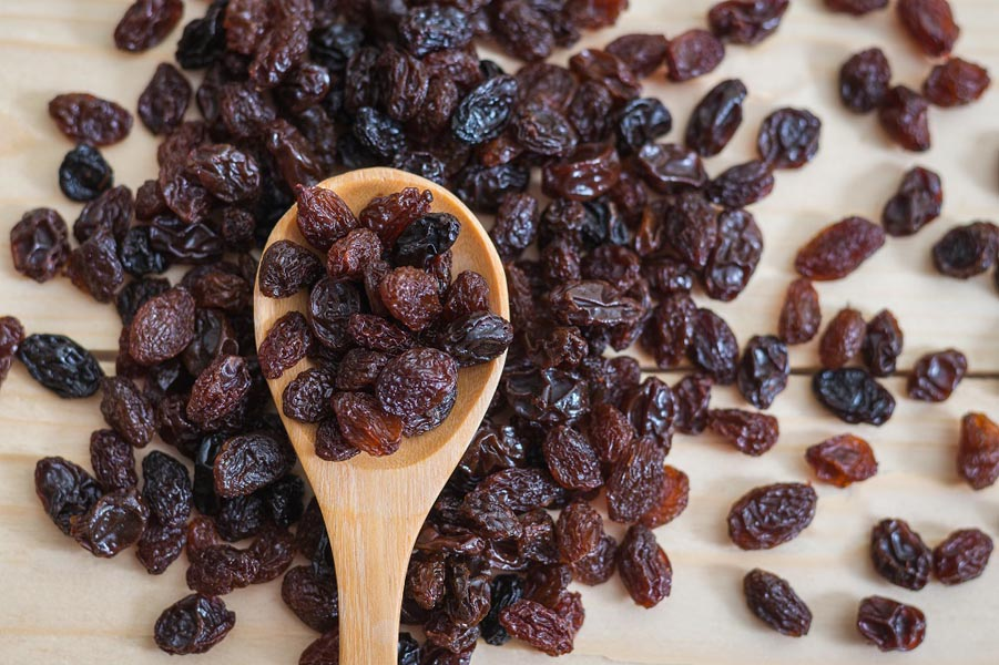 Raisins in a wooden spoon
